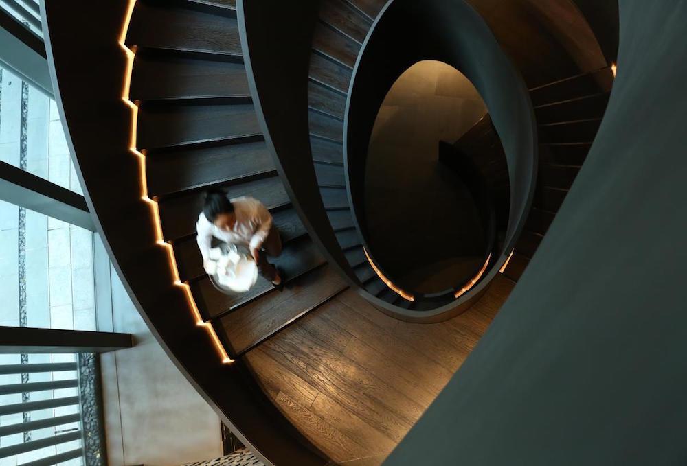 woman walking down modern staircase