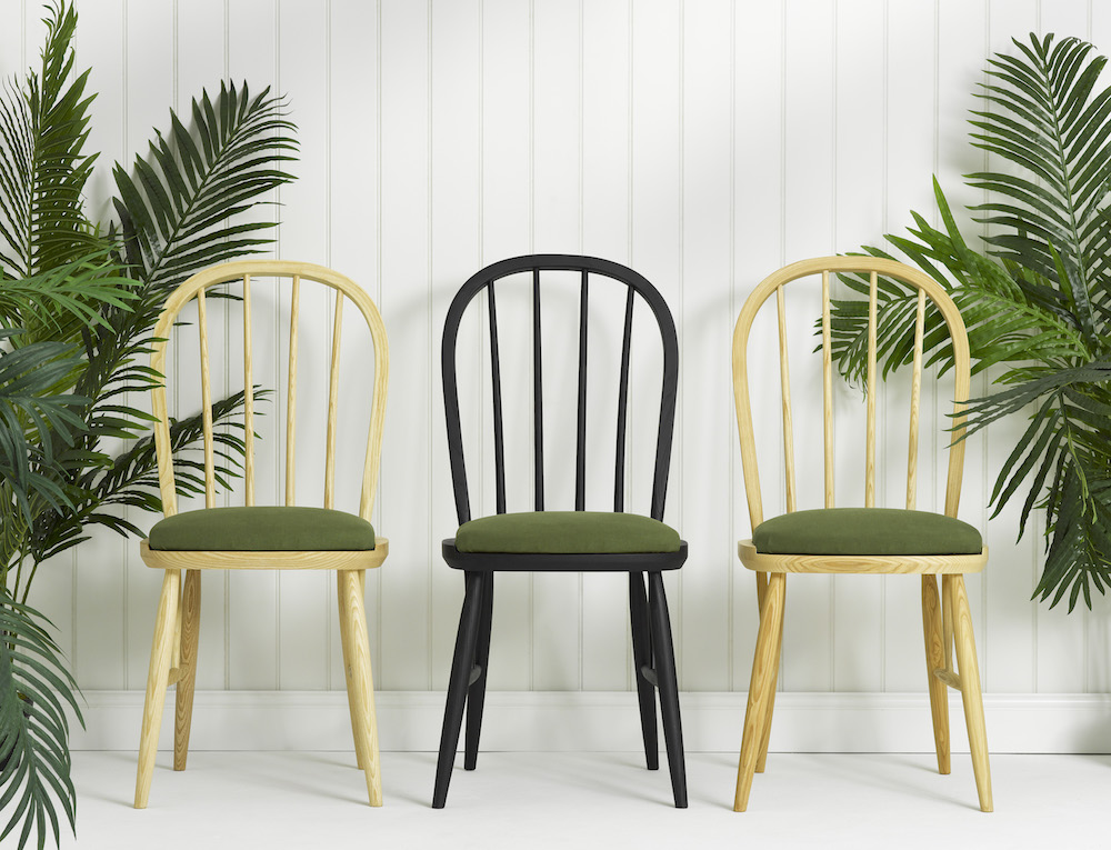 Three wooden chairs next to green plants