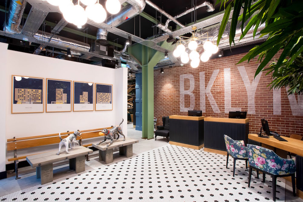 A modern lobby with white and black flooring, brick wall and exposed ceiling with 'Brooklyn' in white