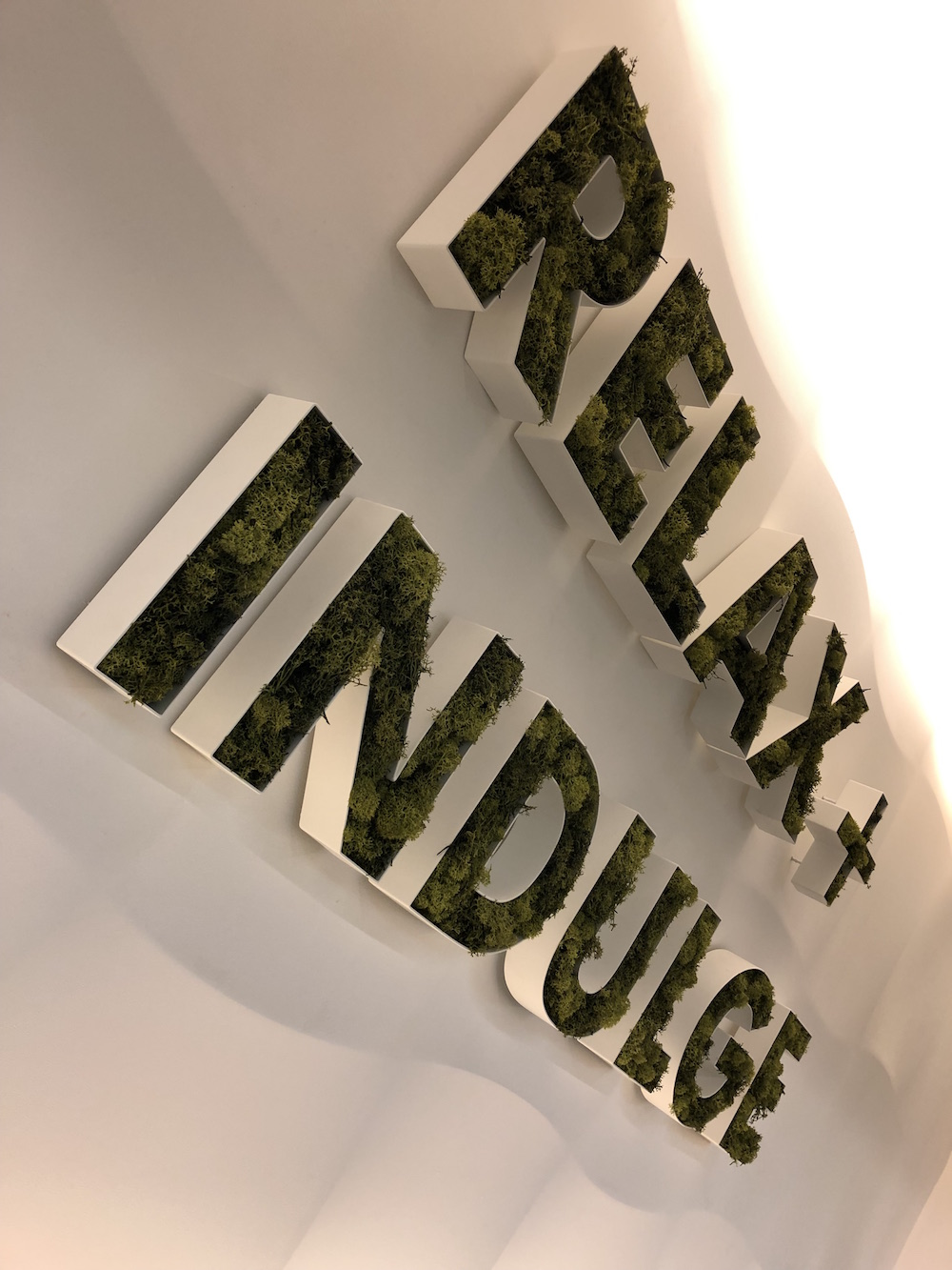 A 'relax + indulge' sign made out of plants