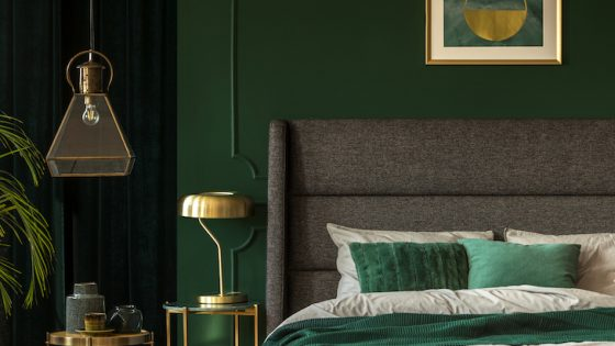 Stylish emerald green and golden poster above comfortable king size bed with headboard and pillows in dark green bedroom