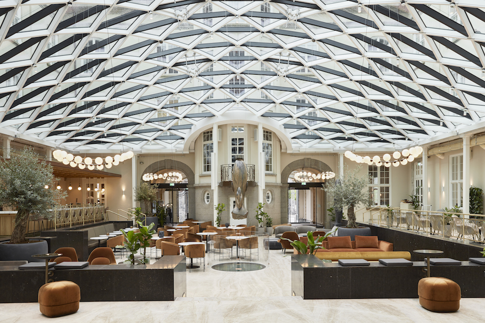 A large lobby with glass ceiling and modern furniture