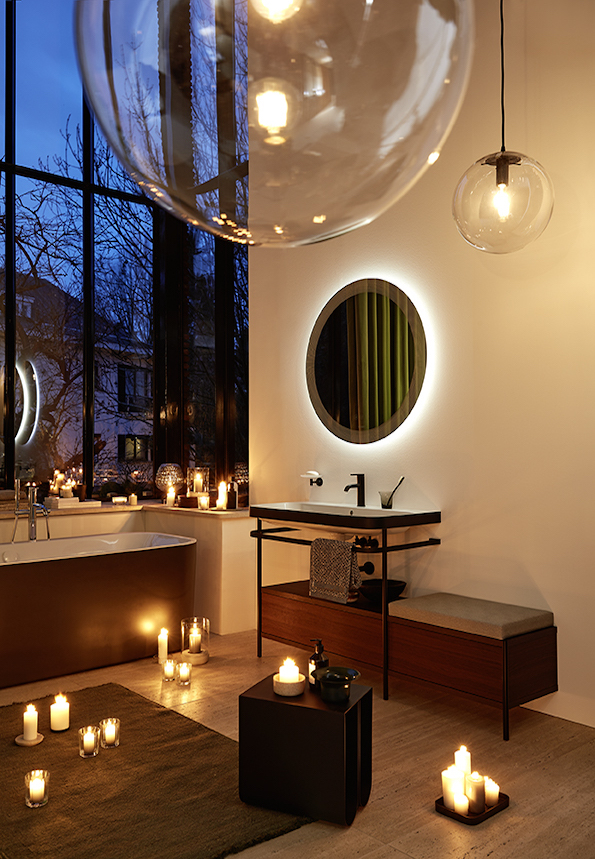 "Image caption: Bathing in warm light and warm water: a warmly lit bathroom creates a cozy place of refuge, especially during the coldest season. Here: Ambient light at the Happy D.2 Plus mirror in the ""Radial"" finish (graphic- radiating). Design: sieger design. 