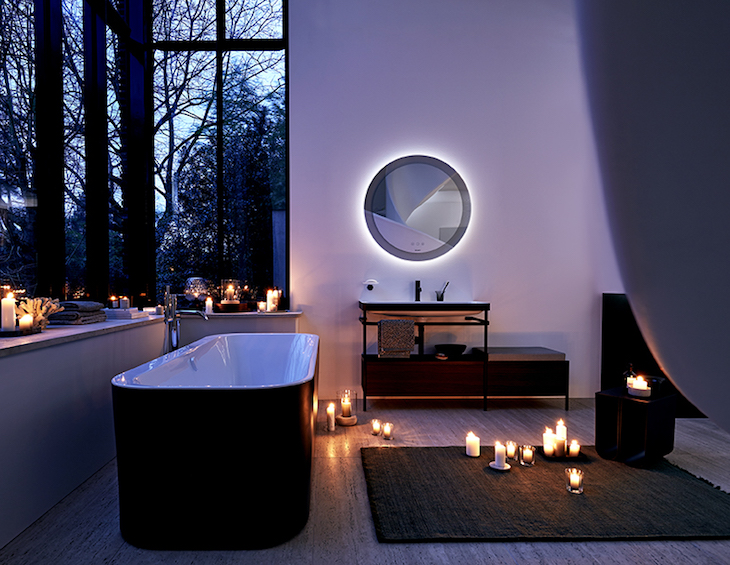 A purple lit bathroom with black bath and candles on the floor