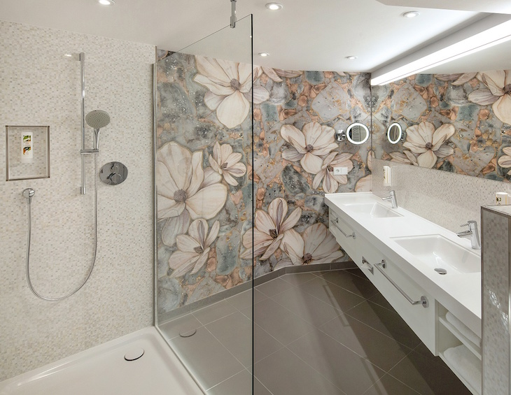 A bathroom with floral walls and modern shower unit from Kaldewei