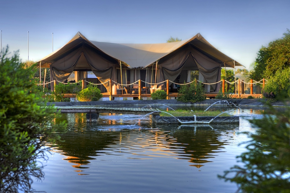 A tented accommodation in front of a river