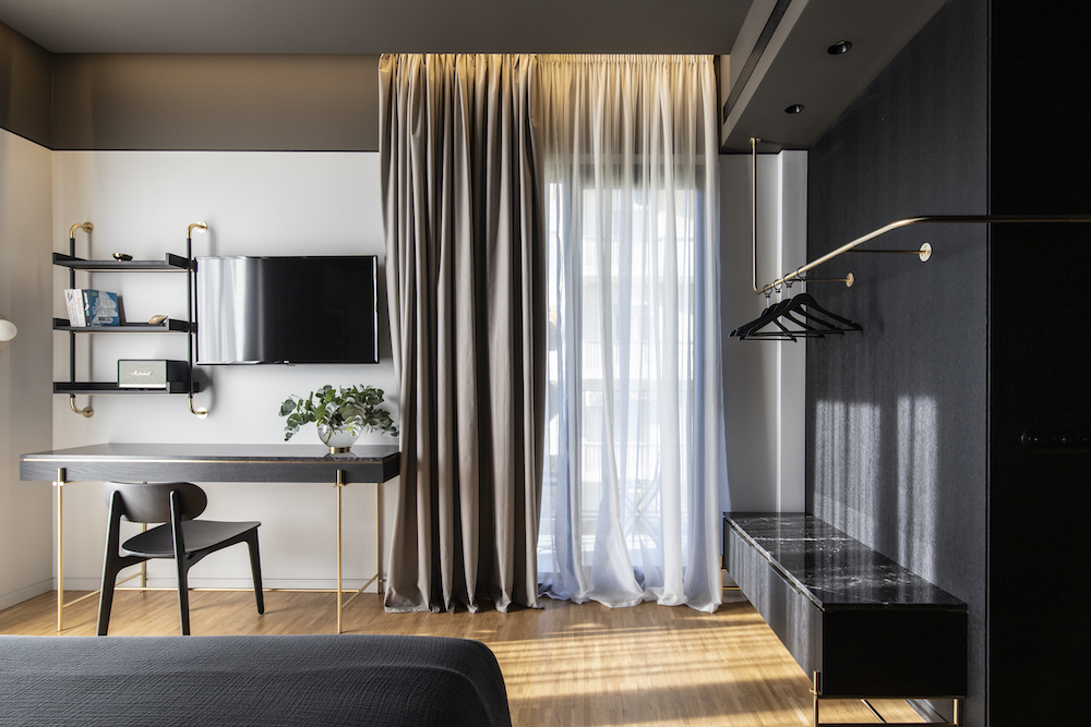 An image showing exposed wardrobe and work area inside suite - The Modernist in Athens