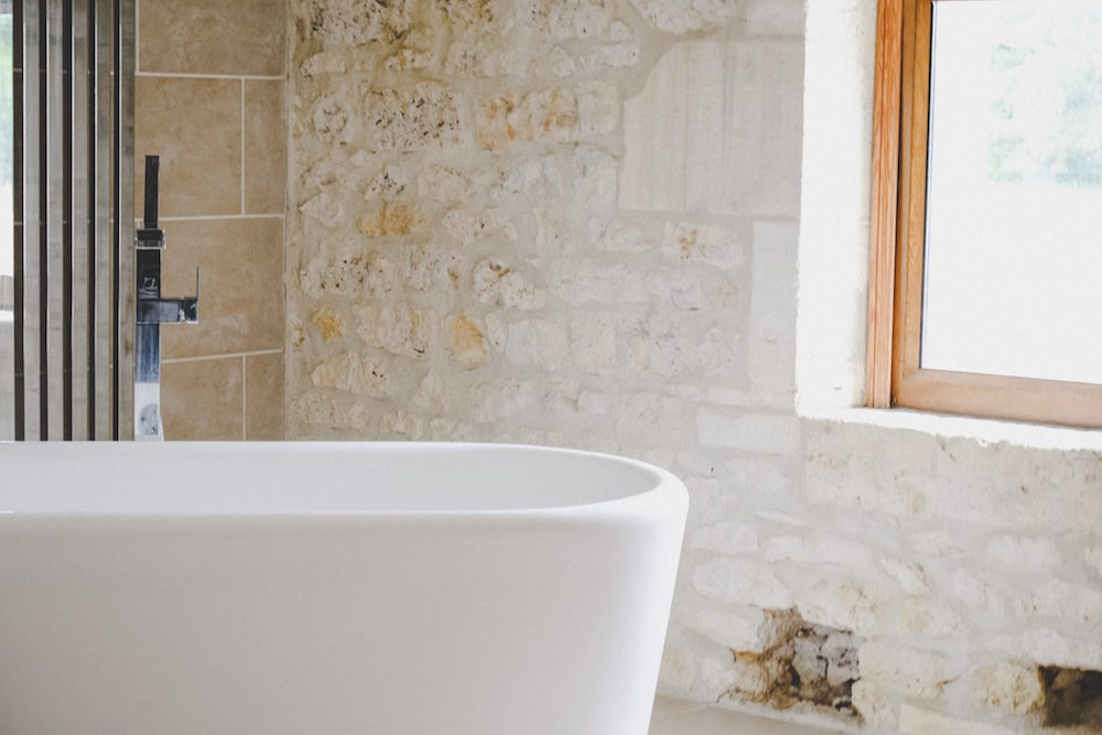 A modern bath with stone walls