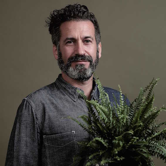 An image of Oliver Heath holding a a plant
