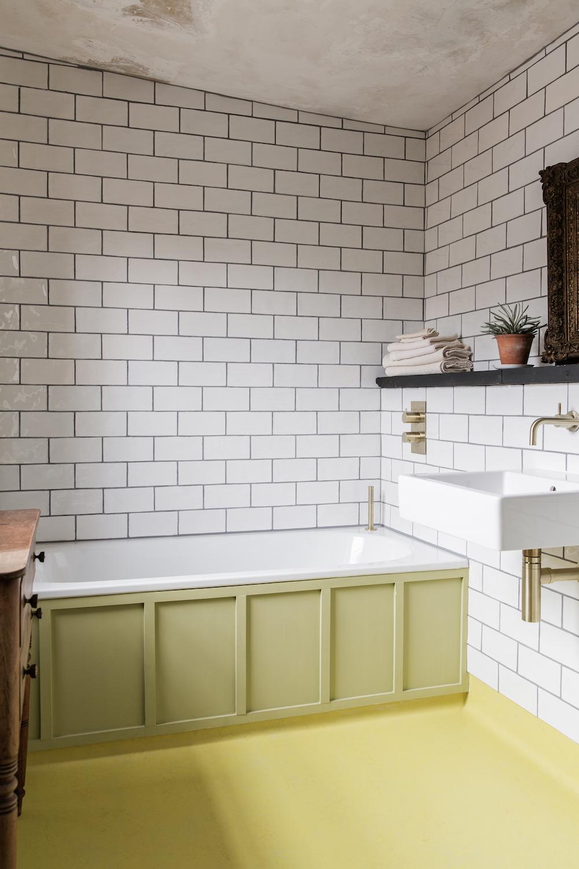 A white brick bathroom with green bath