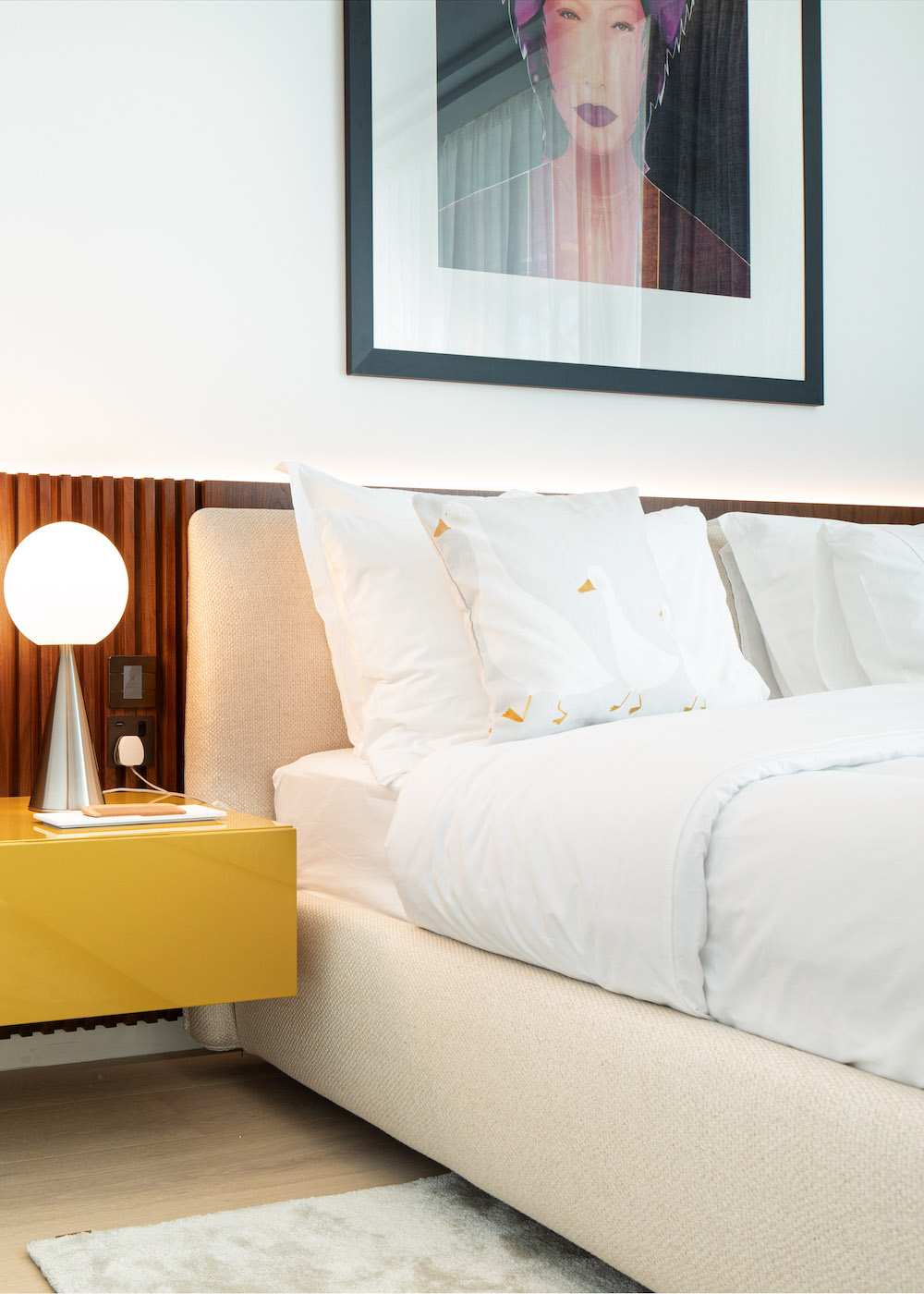 A yellow bedside table and white bed