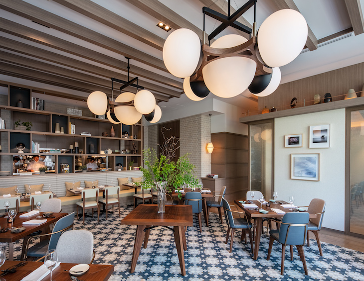 A contemporary dining area in a hotel with bold orb lighting