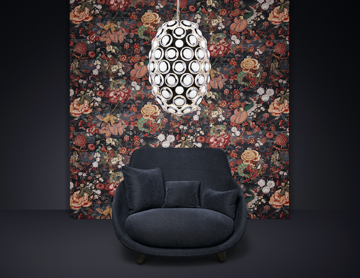An artistic wallcovering behind blue armchair