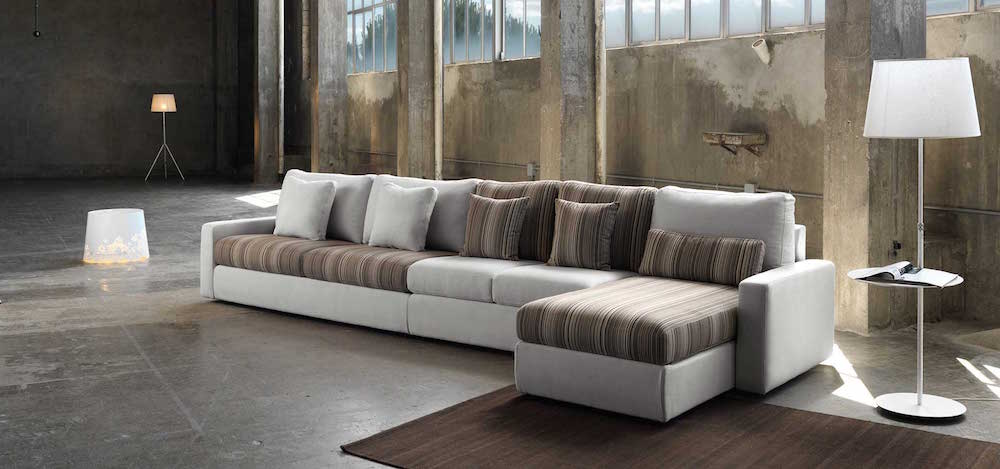 A large L-shaped sofa in a deserted warehouse