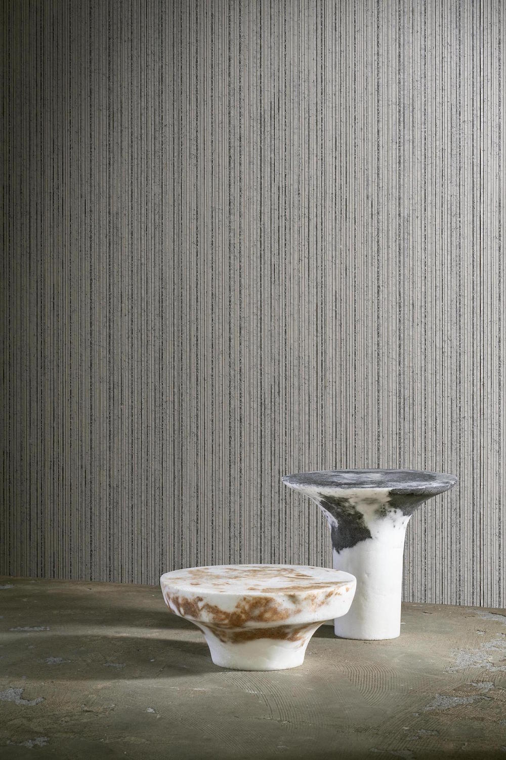 A bare room with two small tables featuring Arte wallcovering