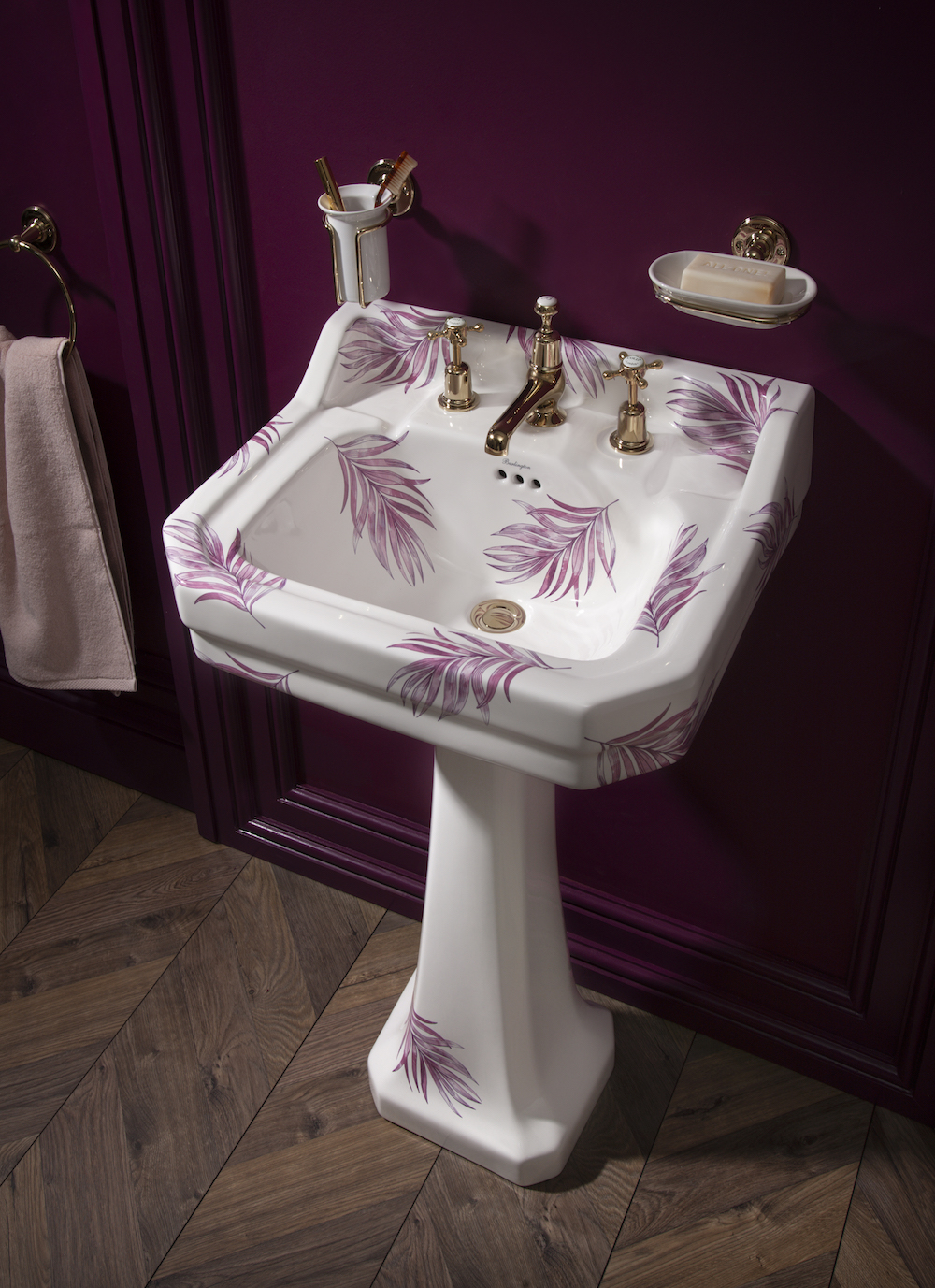 A white basin with pink features painted on
