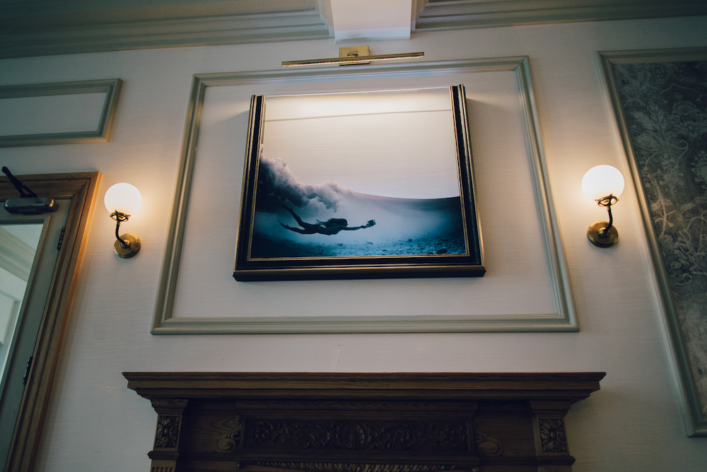 An image above a fireplace of a woman diving underwater