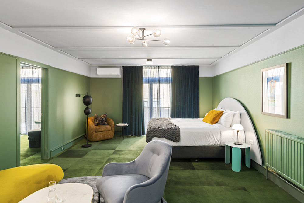 A large green contemporary hotel suite