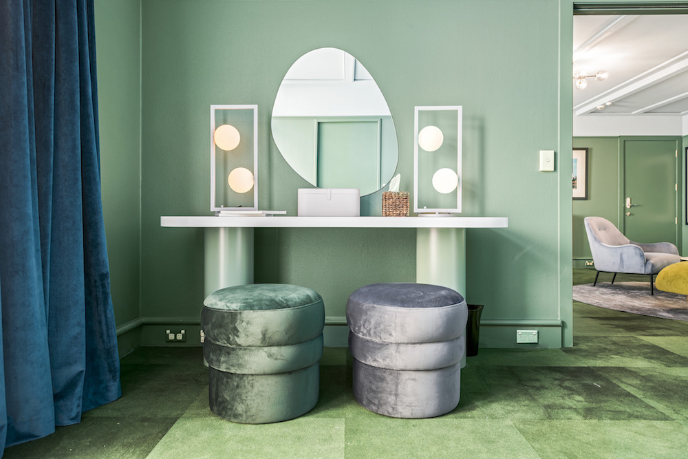 A vanity area inside a large green hotel suite