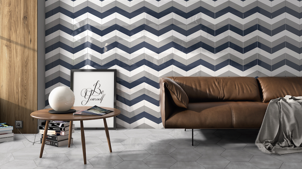 A leather sofa in front of a zig-zag wall tiles in blue, grey and white.