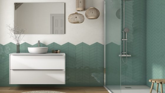 A modern bathroom that is half tiled in green