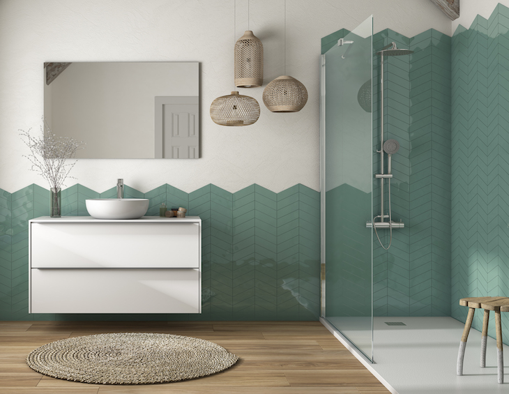 A modern bathroom that is half tiled in green