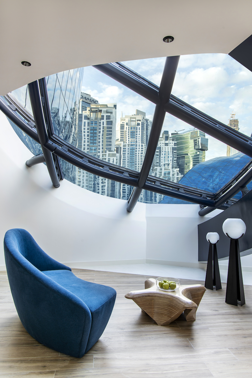 A blue chair next to fluid window designed by Zaha Hadid