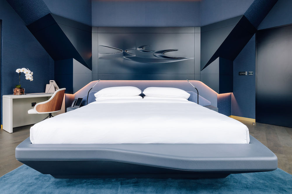 A moody and masculine themed hotel room, designed by Zaha Hadid