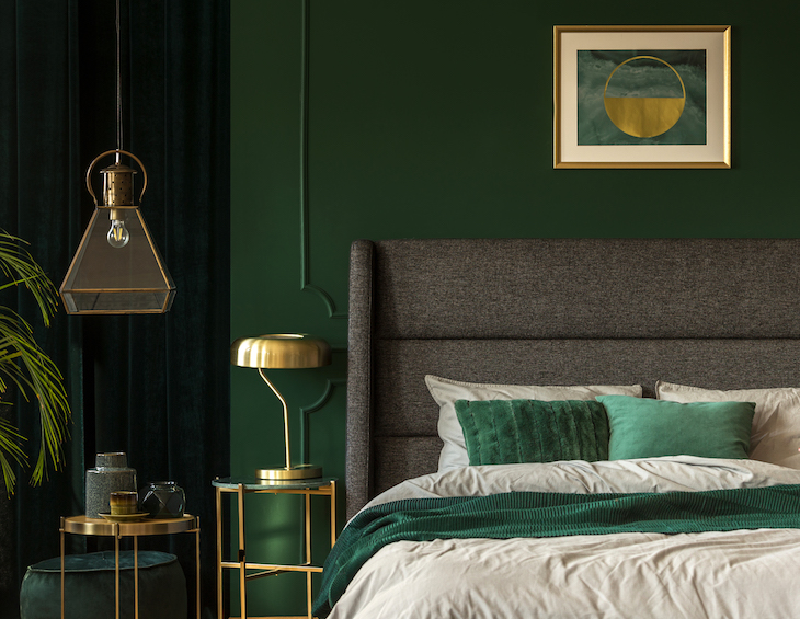 Stylish and sustainable emerald green and golden poster above comfortable king size bed with headboard and pillows in dark green bedroom