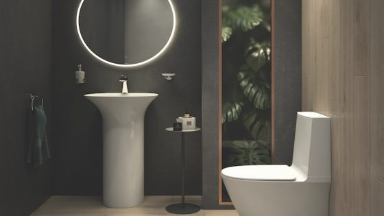A dark-lit modern bathroom with circular mirror and modern toilet