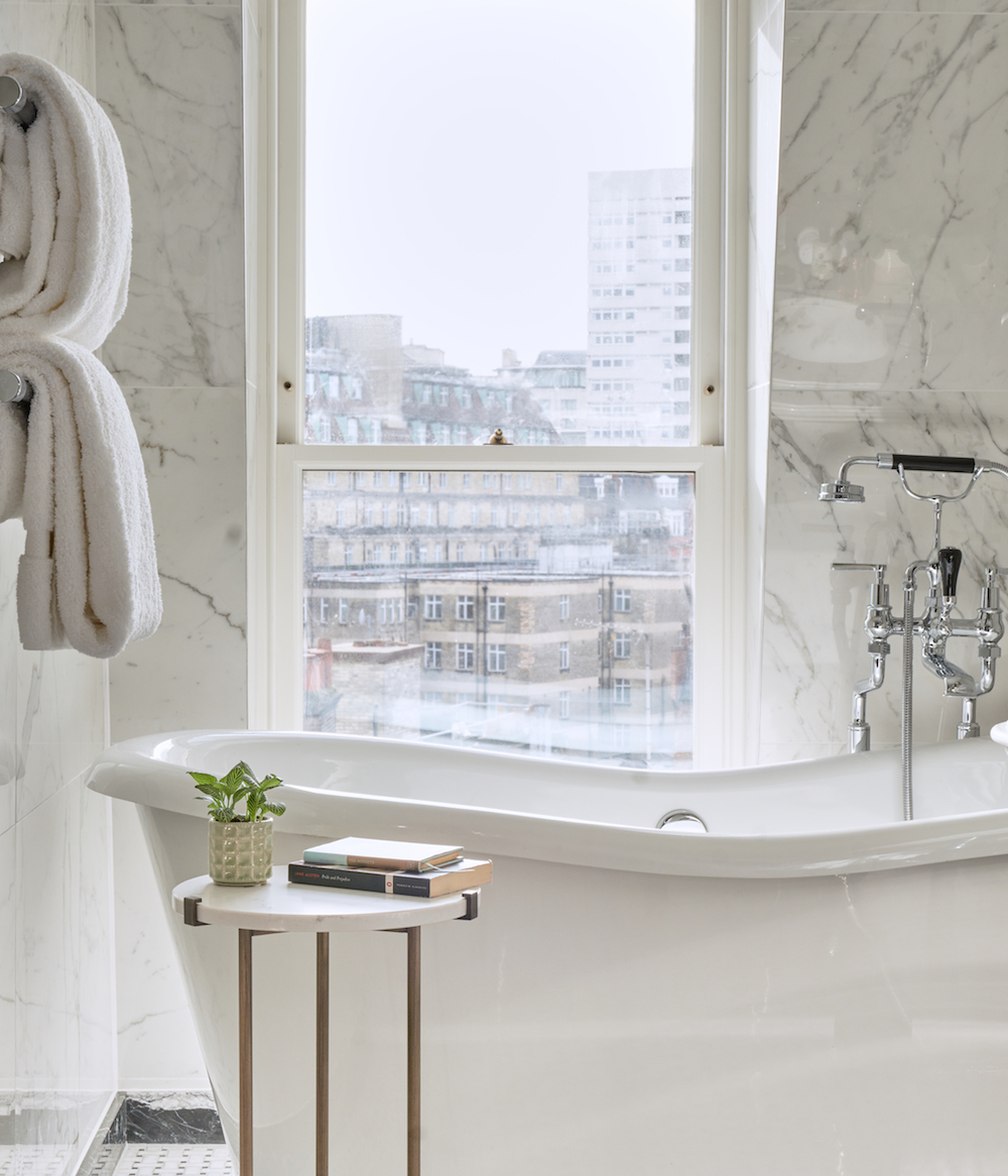 A white roll-top bath in a marble bathroom inside The Mayfair Townhouse