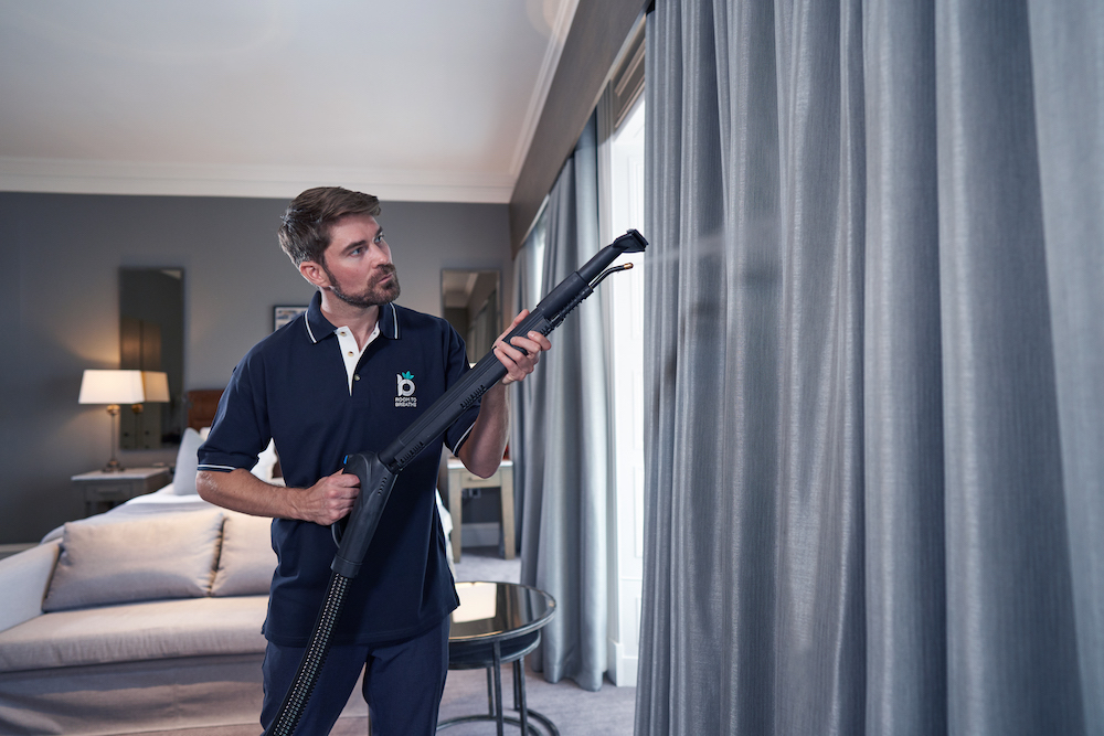Man using hygiene friendly way to steam clean curtains