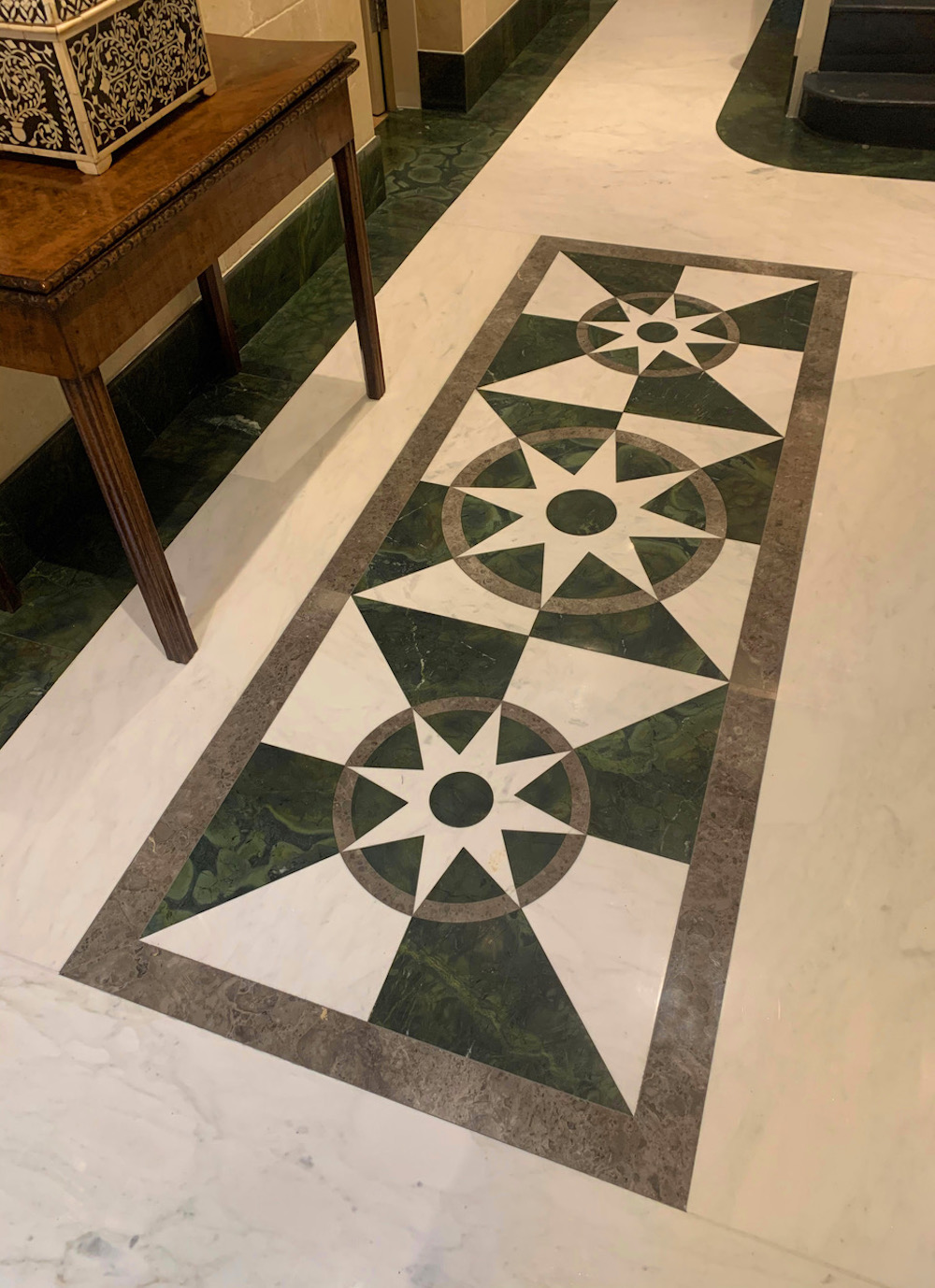 Image caption: The polished marble and quartzite floor is finished and polished, and incorporates a water-jet cut central panel design with a relatively traditional orientation, with a nod to mapping imagery as point of reference.