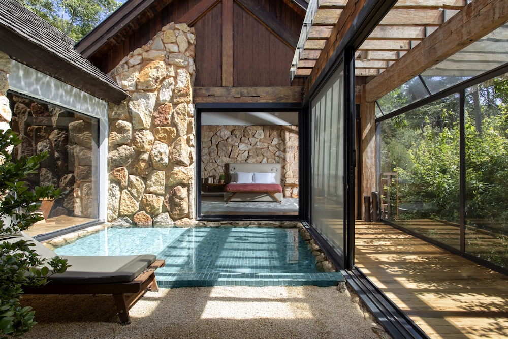A luxury villa that shows a indoor private pool with stone surfaces
