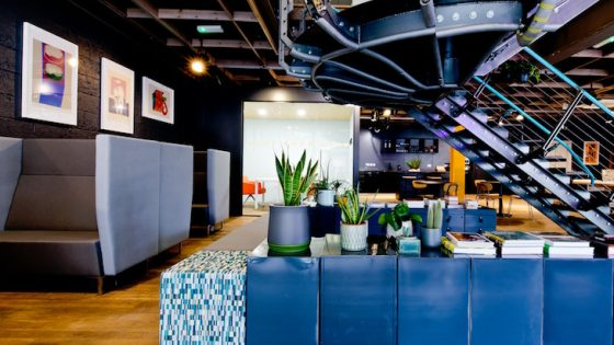 Colourful and quirky lobby/lounge in hotel with blue furniture and industrial stairs
