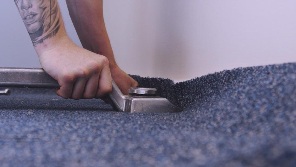Close up image of a man installing a carpet