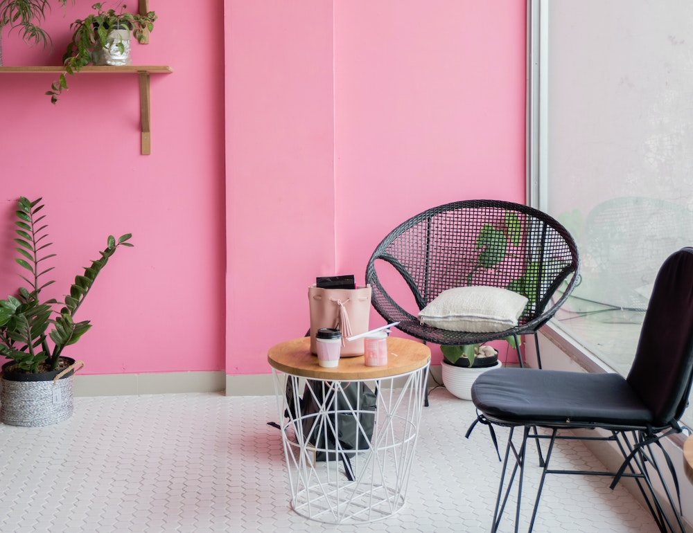 Image of pink colour on walls and black outdoor furniture indoors