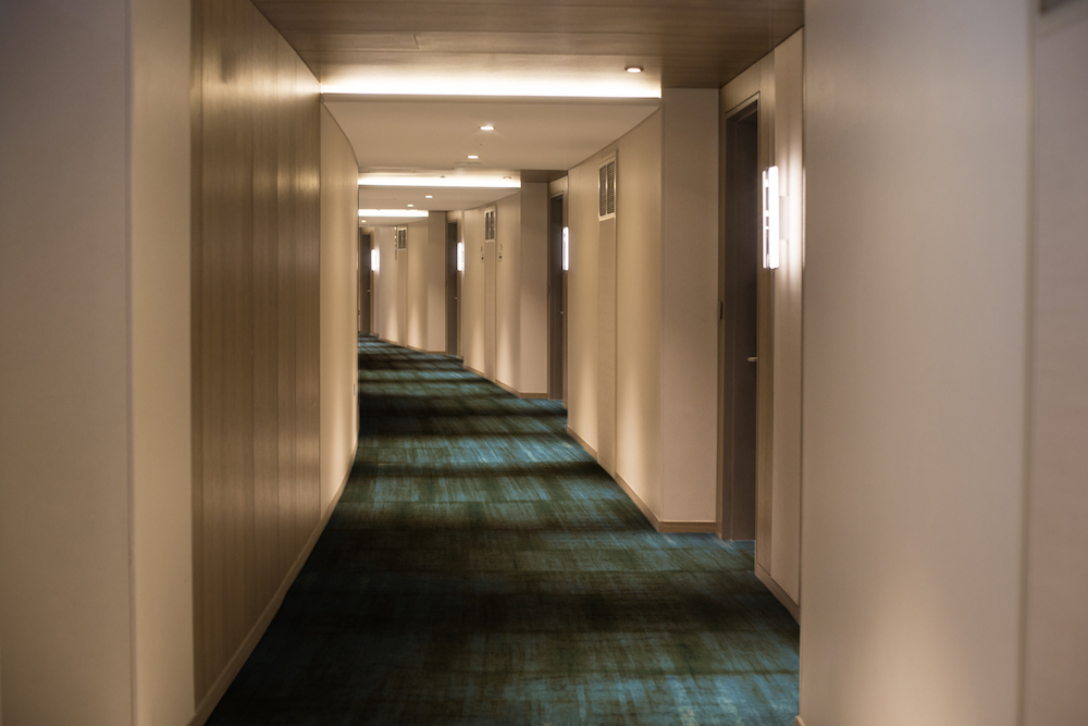 long corridor in a hotel with blue/green carpet