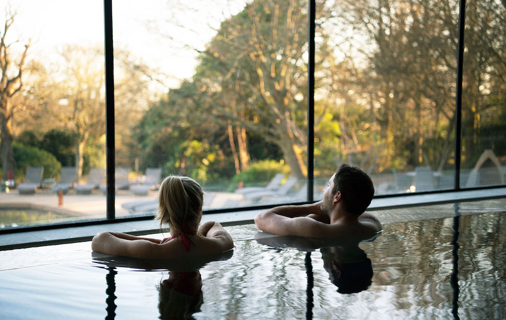 Image of two people in pool overlooking nature outside