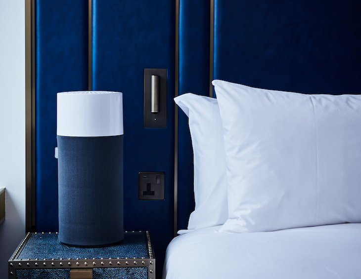 A navy blue air purifier next to a navy blue bed