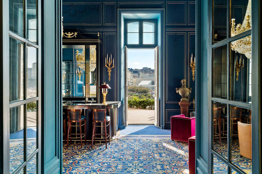 Interior design image of green/blue walls and doors overlooking town