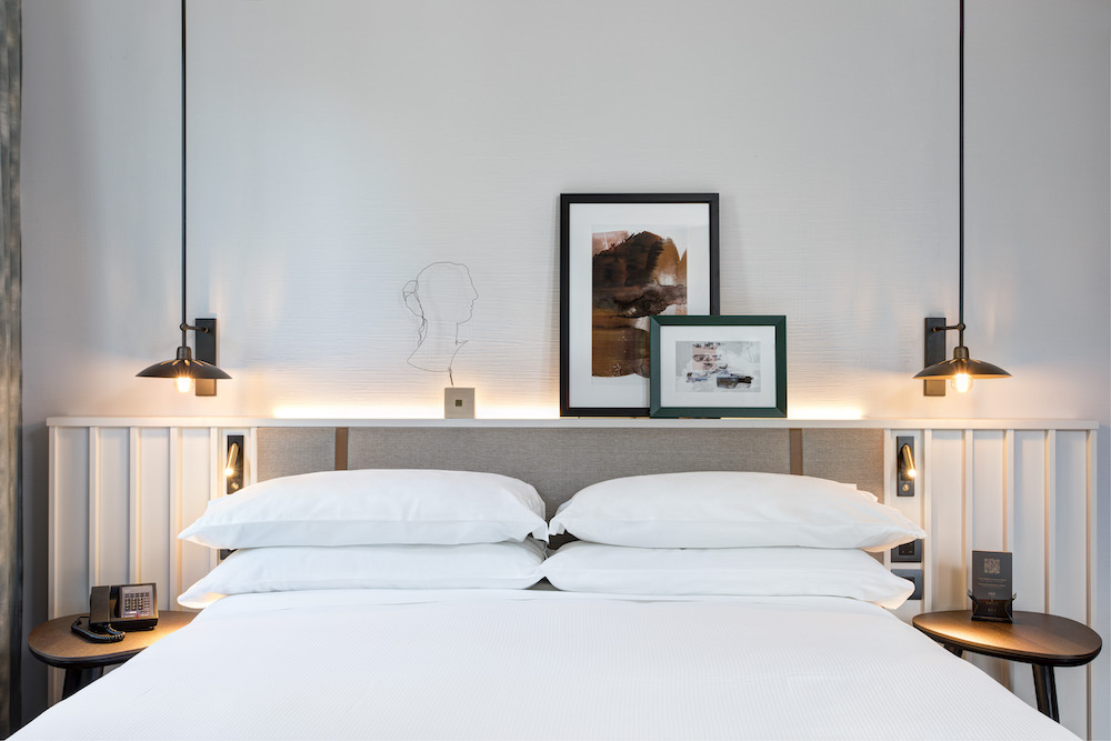A white room with a few pictures on headboard in DoubleTree by Hilton Rome property