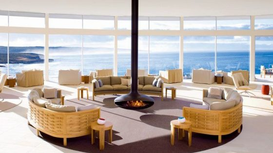 Image of luxury public area with fire in the middle of room over looking an incredible sea view