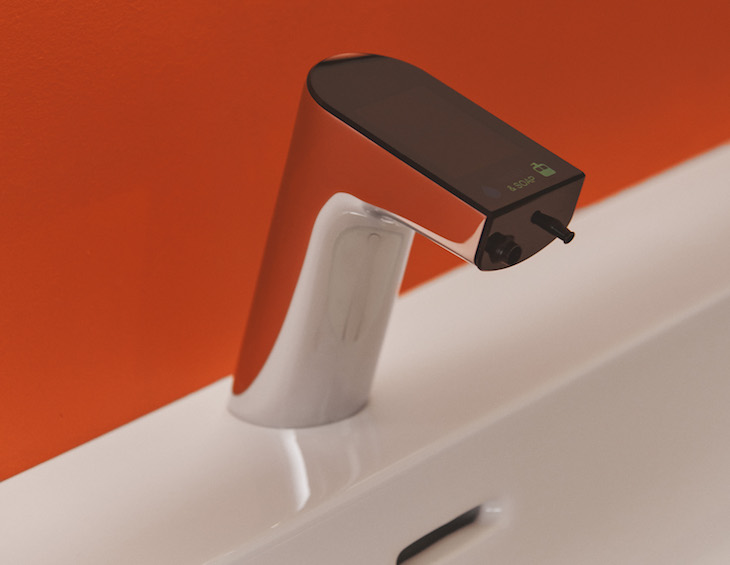 Close-up of a digital tap with orange walls