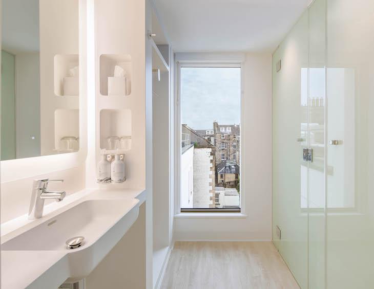 Contemporary bathroom inside YOTEL Edinburgh framing views of the Old Town