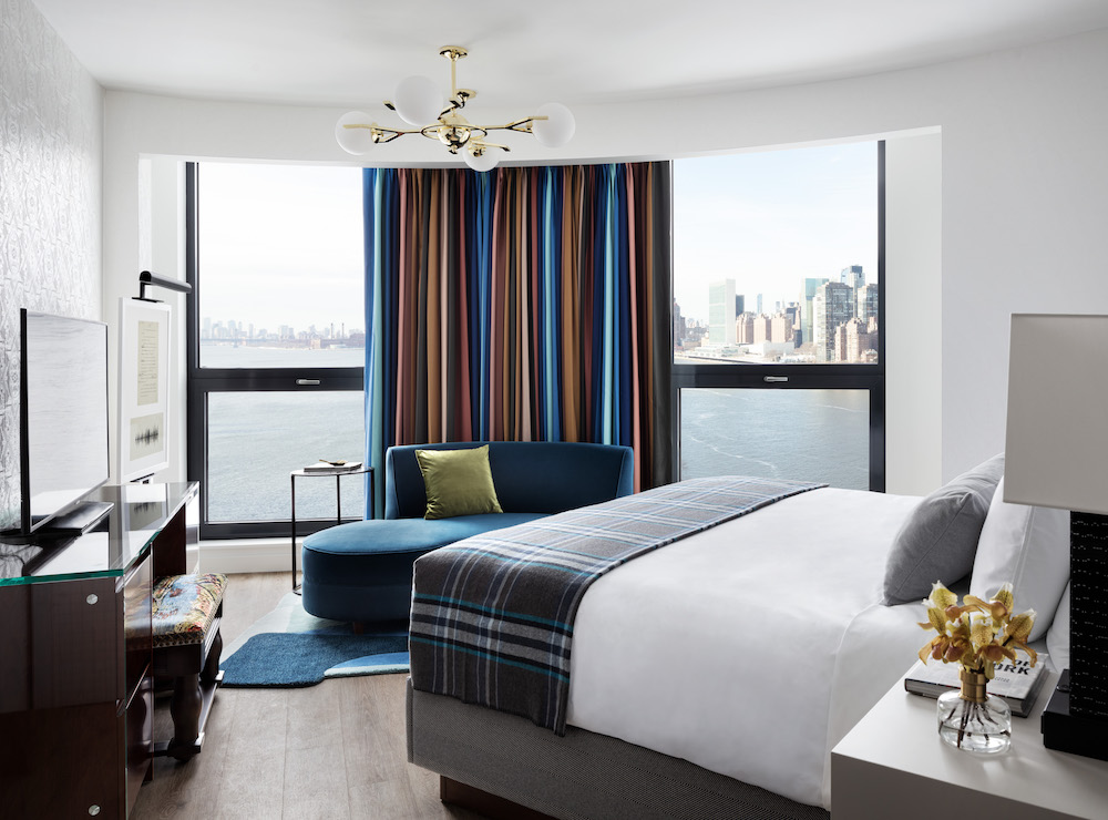 A soft, contemporary guest room overlooking the river in New York