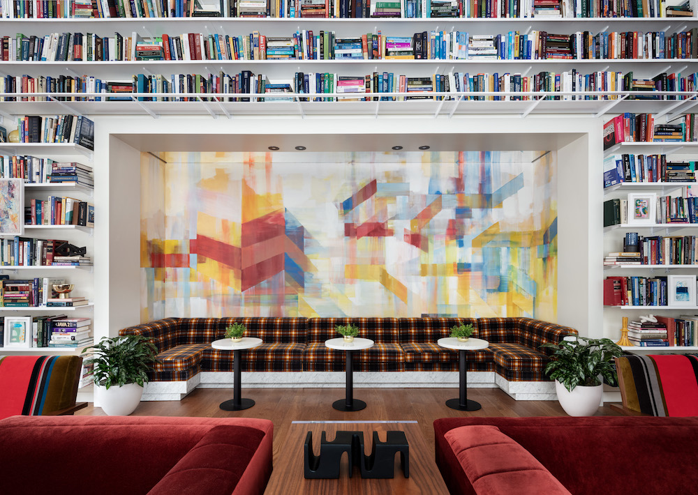 book shelf framing seating in lobby with deep red sofas in lobby of Roosevelt Island hotel