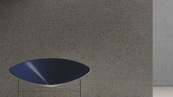 Image of blue modern chair next to cork wallpaper