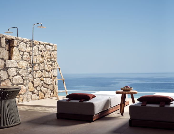 A private outdoor bathroom and sunbeds overlooking sea