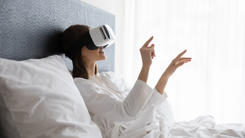 Amazed young woman sit wake up in white bed wearing virtual reality glasses, stunned millennial girl awaken rest in hotel or home bedroom try experience VR googles, modern technology concept